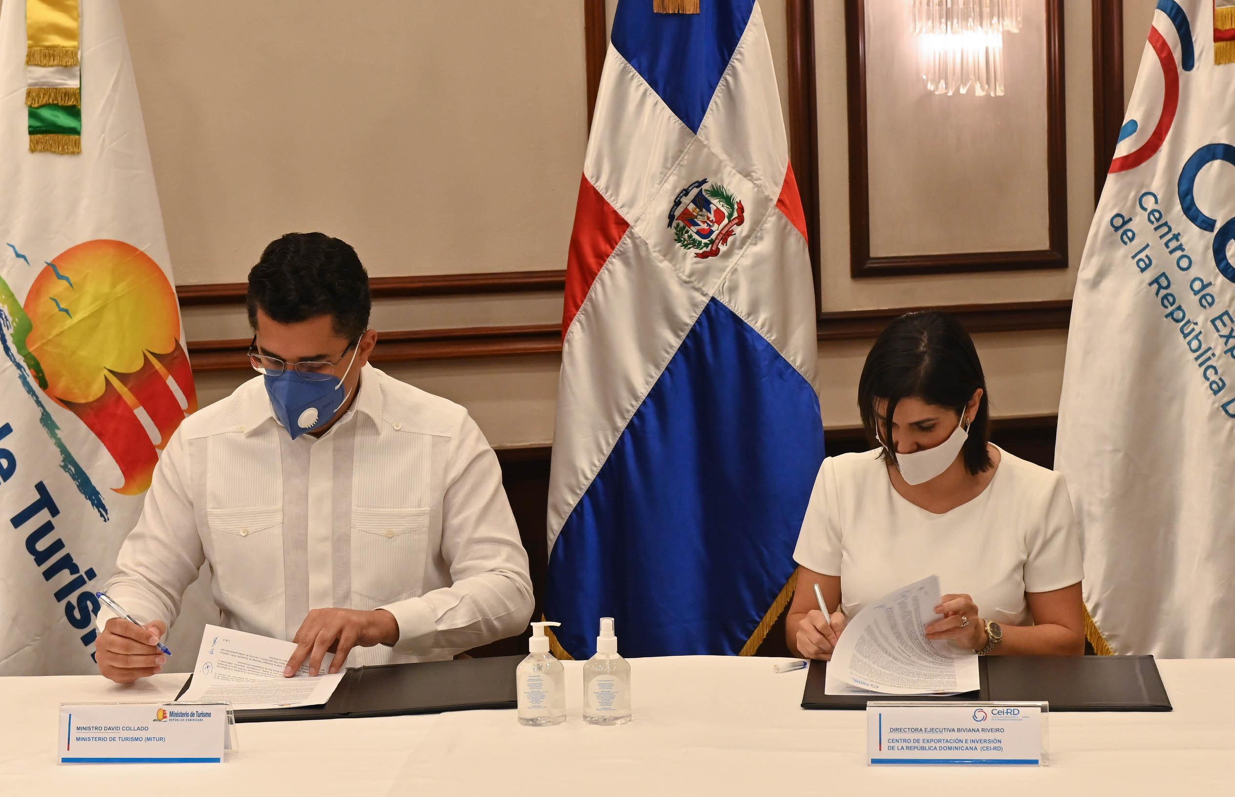 el ministro de Turismo, David Collado y la directora del Centro de Inversión y  Exportaciones (CEI-RD), Biviana Riveiro Disla durante la firma del acuerdo.