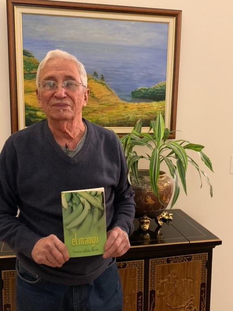 Frank Morales posa mostrando su libro El Mangú